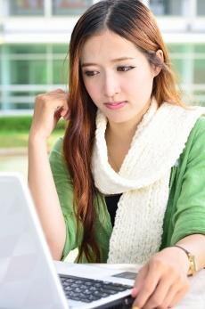 симпатичная девушка увлеченно  работает за ноутбуком