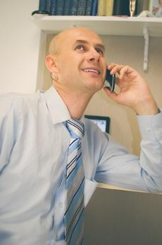 сотрудник компании с улыбкой ведет переговоры по телефону