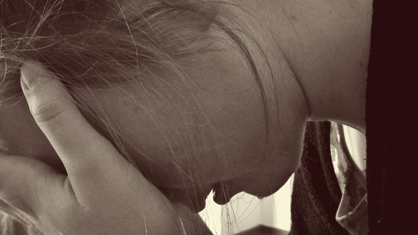 девушка прижимает лоб к ладоням в состоянии разочарования